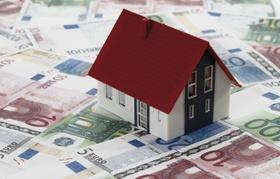 Kleines Hausmodell steht auf Geldscheinen