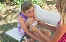 Kleines Mädchen bekommt von erwachsener Person ein Pflaster auf verletztes Knie geklebt