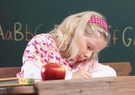Kleines Maedchen im Klassenzimmer beim Schreiben