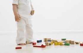 Kleinkind steht vor umgeworfenen Bauklotzturm