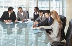 Kollegen an Konferenztisch diskutieren