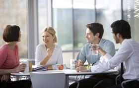Kollegen sitzen essend an Tisch und unterhalten sich