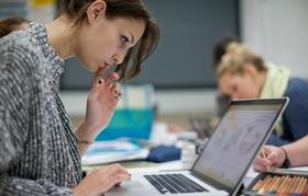 Konzentriert aussehende Studentin arbeitet an Laptop