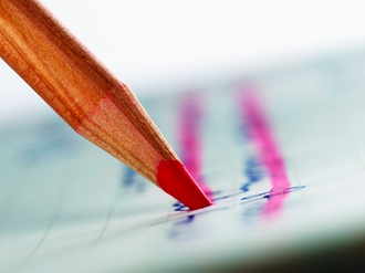 Close Up of a Red Colouring Pencil Crossing Out Handwriting on a Piece of Paper