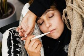 Kranke Frau mit Fieberthermometer im Mund