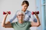 Krankengymnastik, Therapeutin und ältere Frau mit Hanteln