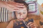 Krankes Kind mit Thermometer im Mund