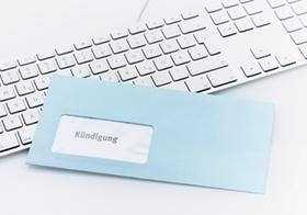 Blauer Kündigungsbrief liegt auf Tastatur