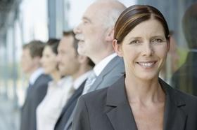 lächelnde Frau im Vordergrund, Frau und zwei Männer im Hintergrund