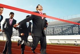 Läufer im Anzug der das Gewinnerband passiert