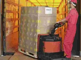 Lagerarbeiter verlaedt Kartons mit Hubwagen in Lkw