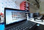 Laptop groß im Vordergrund auf Schreibtisch - dahinter Ablagekörbchen, Kalender und Wandregal