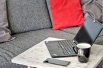 Homeoffice: Laptop, Kafeetasse und Smartphone liegen auf Wohnzimmertisch