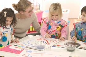 Lehrerin mit Kindern am Tisch beim Malen