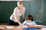 Lehrerin und Schüler vor Tafel
