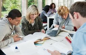 Lerngruppe an Tisch mit Laptops und Bücher