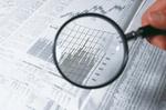 Lupe auf Zeitung mit Aktienkurve_John Foxx Images
