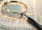 Lupe liegt auf Börsenkursen in Zeitung