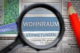 Lupe und Rotstift über der Zeitungsrubrik Wohnungen