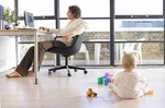 Man using computer by window in home office, side view, baby girl (21-24 months) on floor, rear view