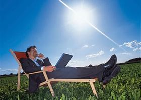 Manager liegt mit Notebook und Handy im Liegestuhl auf Wiese