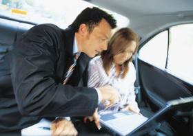 Manager mit Sekretaerin im Auto