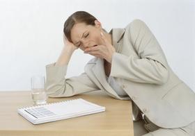 Managerin sitzt muede und gaehnend am Schreibtisch