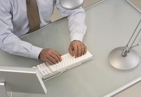 Mann am Schreibtisch mit Tastatur