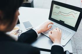 Mann arbeitet an Laptop mit Grafiken