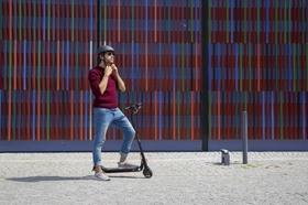 Mann auf E-Scooter vor Gebäude
