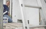 Mann auf Gerüst streicht Hauswand