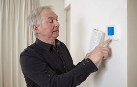 Alter Mann bedient mithilfe einer Bedienungsanleitung kleinen Bildschirm an der Wand