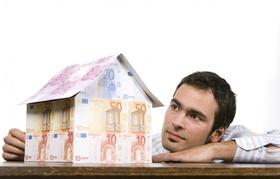Mann betrachtet aus Geldscheinen gebasteltes Haus