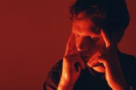 Mann fasst sich mit den Fingern an die Schläfen