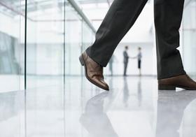 Mann geht am Gang eines Bürogebäudes, Detail Beine