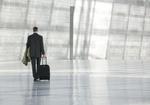 Mann geht mit Trolley-Koffer durch große Halle