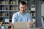 Mann guckt erstaunt in sein Laptop