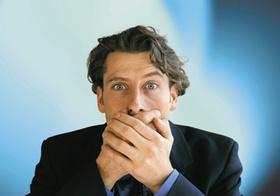 Mann hält beide Hände vor dem Mund