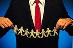 Mann hält Kette aus Papiermännchen aus Dollarscheinen in den Händen