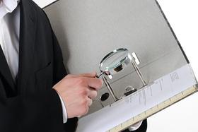 Mann hält Lupe über Dokument in einem Aktenordner