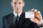 Mann hält Scheckkarte vor sich in der Hand