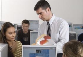 Mann mit Hemd und Krawatte zeigt jungen Leuten Lehrbuch am Computer