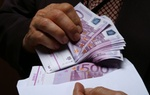 Mann holt 500 Euro Geldscheine aus Briefumschlag