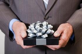 Mann im Anzug hält Geschenk auf Bauchhöhe