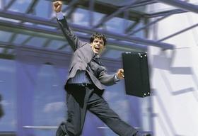 Mann im Anzug mit Koffer springt in die Luft