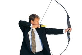 Mann im Anzug schießt mit Pfeil und Bogen