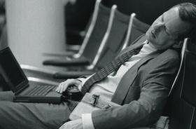 Mann im Anzug schläft auf Stuhl