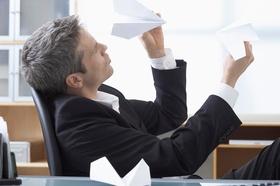 Mann im Anzug sitzt am Schreibtisch und baut Papierflieger