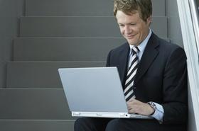 Mann im Anzug sitzt auf Treppe und surft mit Laptop im Internet