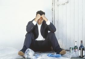 Mann im Anzug sitzt depressiv am Boden